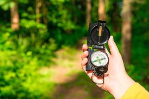 kompass i en kvinnlig hand förlorad i skogen foto