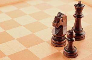 tre träschackstycken på ett schackbräde foto