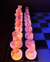 glasschack på schackbrädet tänd av blått och orange ljus foto