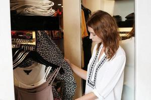ung kvinna väljer kläder i garderoben foto