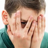 tonåring täcker ansiktet med händerna foto