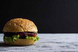 hamburgare på den mörka bakgrunden foto