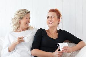 mamma och dotter som sitter på soffan hemma foto