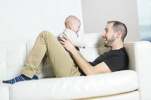 far med baby i soffan som tar sig god tid foto
