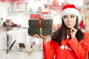 nyfiken julflicka med presenter i presentbutik foto