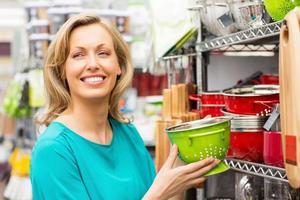 kvinna med en grön emalj durkslag foto