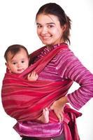 mamma som bär sitt barn i en sele