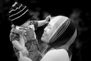 glad mamma som håller sitt barn foto