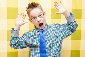 porträtt av en rolig liten pojke som gör ansikte foto