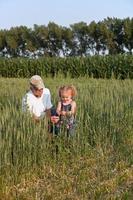 flicka & morfar i vetefält foto