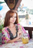 underbar rödhårig modell som dricker färsk drink foto