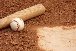 baseboll och fladdermus nära hemmaplattan foto