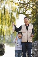 far och son som visar fångst vid sjön
