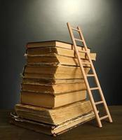 gamla böcker och trestege, på grå bakgrund foto