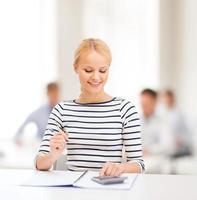 kvinna med anteckningsbok och miniräknare foto