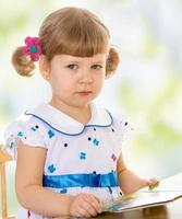 väldigt liten flicka som läser en bok foto