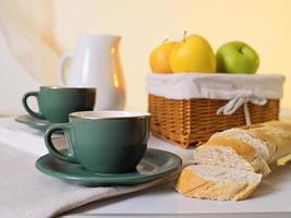 morgonsammansättning med kaffekoppar, bröd och äpplen