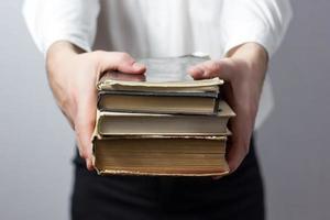 händer som håller böcker isolerad på grå bakgrund foto