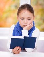liten flicka läser en bok foto