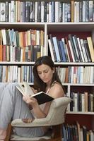 kvinna läser mot bokhyllor foto