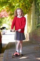 tjej som rider på skoter på väg till skolan foto