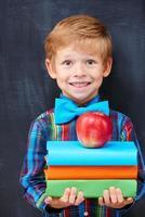 leende uppmuntrad ingefärapojke som håller en hög med böcker foto