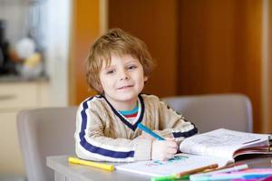söt glad skolbarn hemma gör läxor foto