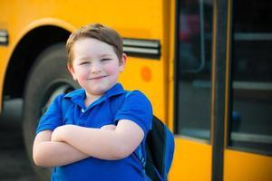 glad ung pojke framför skolbussen foto