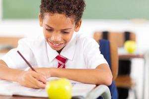 grundskolepojke som skriver klassarbete foto