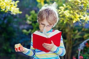 liten pojke med äpple på väg till skolan foto