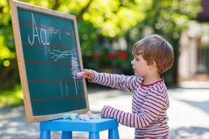 liten pojke på tavlan som utövar matematik foto
