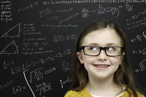 smart ung flicka stod framför en svart tavla