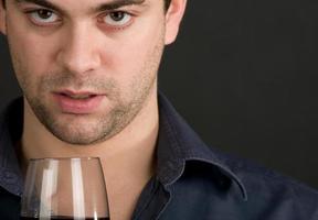 ung man dricker vin foto
