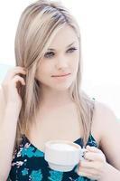 vacker blond tonåring som dricker kaffe foto
