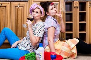 två trötta hemmafru som dricker vin foto