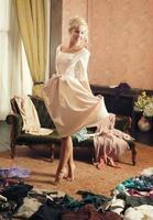 vacker kvinna, omklädningsrum, utspridda kläder foto