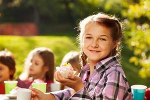 leende flicka håller muffin med sina vänner bakom foto