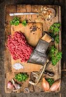 köttfärs av vintage köttkvarn på träbord med örter foto
