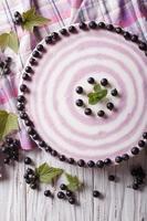 läcker ostkaka med svarta vinbär närbild vertikal topp vi foto