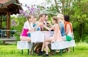 familj och grannar på trädgårdsfest som dricker foto