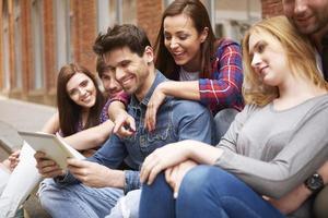 grupp människor som sitter på trottoaren foto