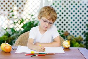 liten pojke med glasögon som gör läxor hemma foto