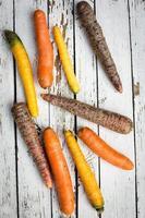 mångfärgade morötter på trä foto