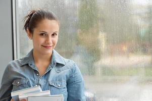student med böcker framför fönstret foto