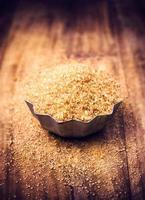 brunt socker för julbakning i skål på träbord,
