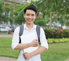 glad leende högskolestudent med bärbar dator foto