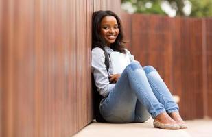 afrikansk college flicka sitter på golvet foto