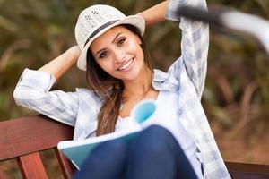 ganska högskolestudent läser bok i parken foto