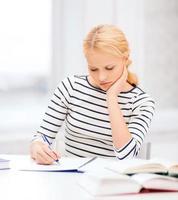 uttråkad studentkvinna som studerar på college foto