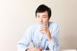 japansk man dricker kraftigt foto